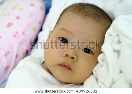 Cute Asian infant baby in beautiful dress lying and looking something on her bed.