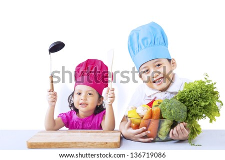 Cute asian kids with vegetables ready to cook isolated on white - stock photo