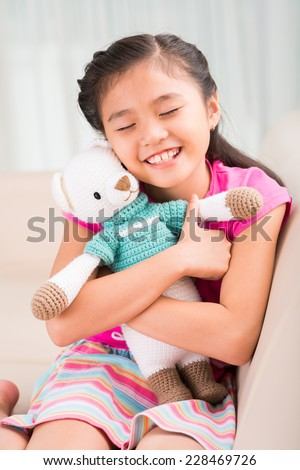 Cute Asian little girl embracing tight her favorite toy - stock photo