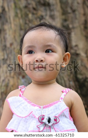 Cute Asian little girl looking up. Sweating on hair after playing. - stock photo