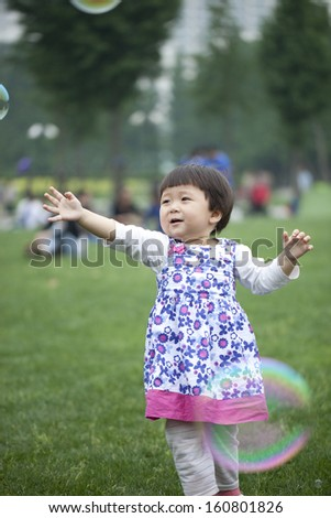 Cute asian little girl plays with a giant bubble outside in the park