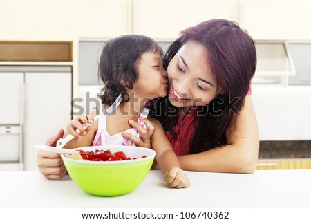 Cute asian little girl with fruit salad kissing her mother. shot in the kitchen - stock photo