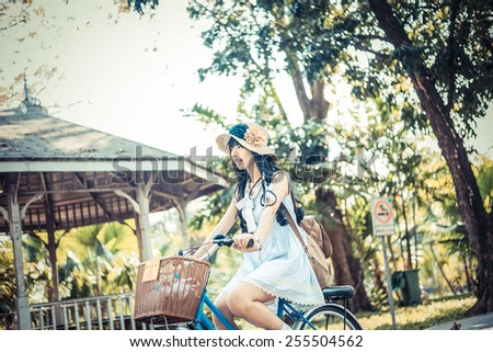 Cute Asian Thai girl in vintage clothing is riding a bicycle, in the sunny summer park in soft vintage style. - stock photo
