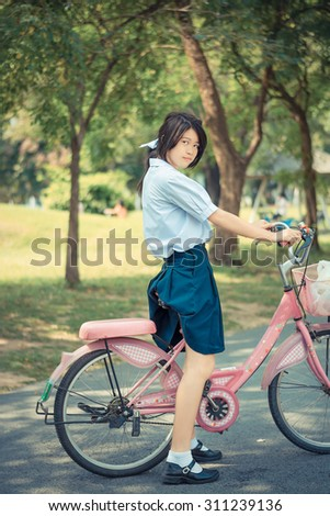 Cute Asian Thai schoolgirl student in high school uniform fashion is standing over her pink bicycle ready to exercise in sunny summer park with green environment in vintage color. - stock photo