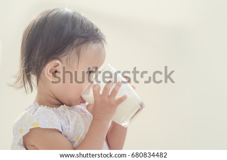 Cute Asian toddler girl drinking milk from a big glass