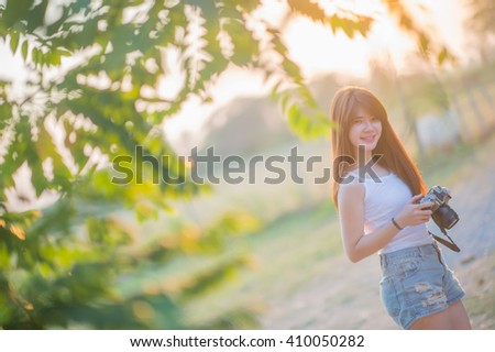 Cute Asian woman with long brown hair holding a camera in the wild in the sunset. - stock photo