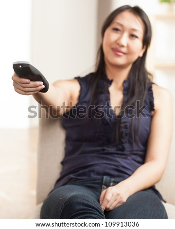 Cute Asian young woman having fun with a remote control. - stock photo