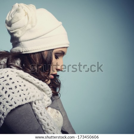 Cute attractive fashion young girl in warm clothes in profile, over blue - stock photo
