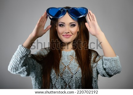 Cute attractive fashion young girl posing with funny big love blue heart glasses. - stock photo