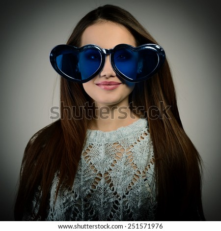 Cute attractive fashion young girl posing with funny big love blue heart glasses, image toned. - stock photo