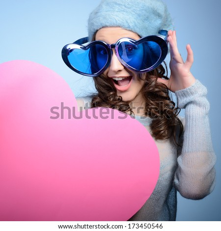 Cute attractive fashion young girl posing with funny big love glasses and pink heart, over blue background - stock photo