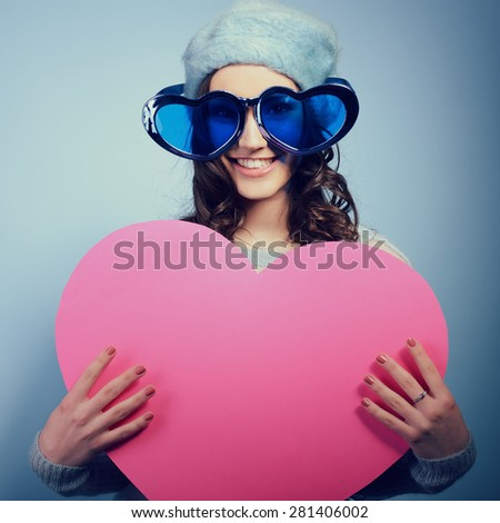 Cute attractive fashion young girl posing with funny big love glasses and pointing at pink heart - stock photo