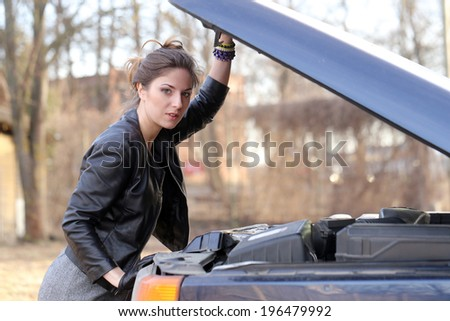 Cute, attractive girl under car hood - stock photo