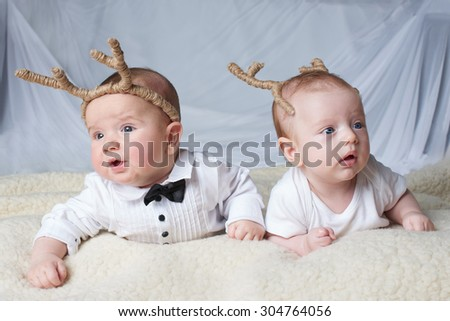cute babies with deer horns on bright background - stock photo