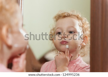 Cute baby applying cream on her cheeks looking at mirror - stock photo