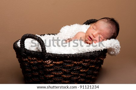 Cute baby asleep in basket with soft lining. - stock photo