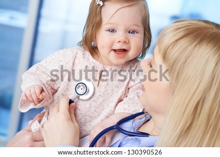 Cute baby being examined by female doctor in hospital - stock photo