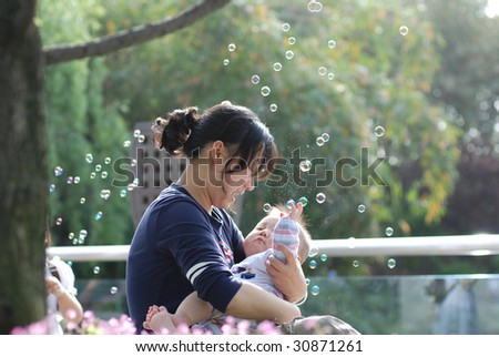 Cute baby boy and  his mother in park with bubbles inbackground - stock photo