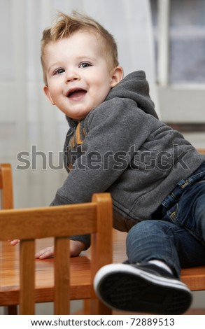 Cute baby boy at 18 months sitting on table at home. - stock photo