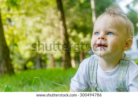 cute baby boy, child, on natural green background - stock photo