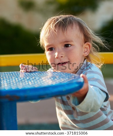 Cute baby boy child playing in play area. Toddler at the playground playpot.
