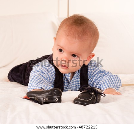 Cute baby boy crawling for his shoes on top of a bed - stock photo