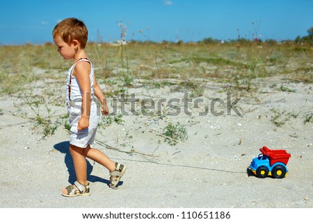 cute baby boy dragging toy car walking at the field - stock photo
