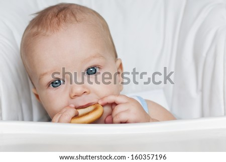 cute baby boy eating a bagel at a table on a white background