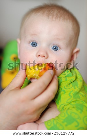 Cute baby boy eating healthy food (peach) - stock photo