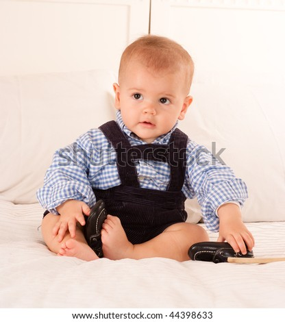 Cute baby boy in blue corduroy trousers and checked shirt sitting on a bed - stock photo