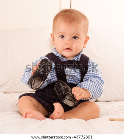 Cute baby boy in blue corduroy trousers playing with his shoes