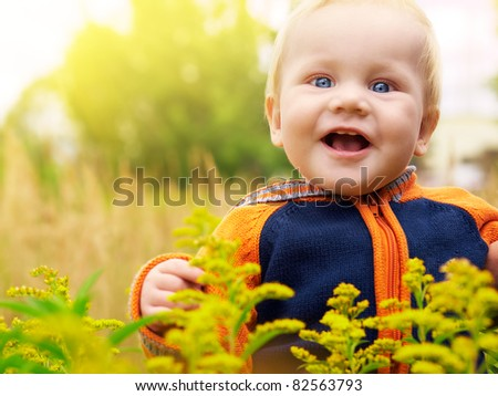 Cute baby boy in field of flowers - stock photo