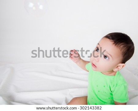 cute baby boy in green clothing looking upwards at soap bubble with adorable big beautiful eyes. - stock photo