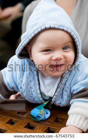 Cute baby boy in hoodie at restaurant - stock photo