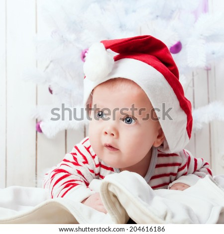 Cute baby boy in Santa`s hat on white blanket under decorated Christmas tree