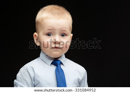 Cute baby boy in shirt, vest and tie with surprised expression. Over black background. Copy space. - stock photo