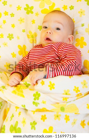 Cute baby boy laying in bed. - stock photo