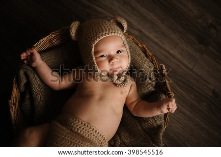 Cute baby boy lie on a beige background wearing a crochet hat, baby bear in a basket - stock photo