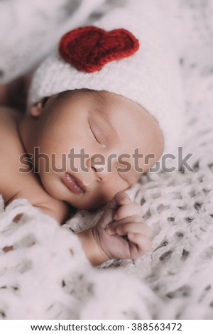 Cute baby boy lie on a beige background wearing a crochet hat with heart saint valentine - stock photo