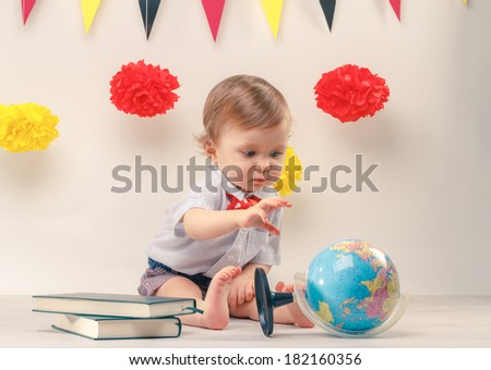 Cute baby boy looking at a earth globe, sitting next to party flags - stock photo
