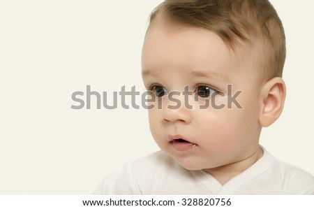 Cute baby boy looking down to the side surprised. Adorable baby portrait looking curious isolated on white. - stock photo