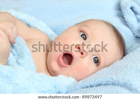 Cute baby boy lying in a soft blanket - stock photo
