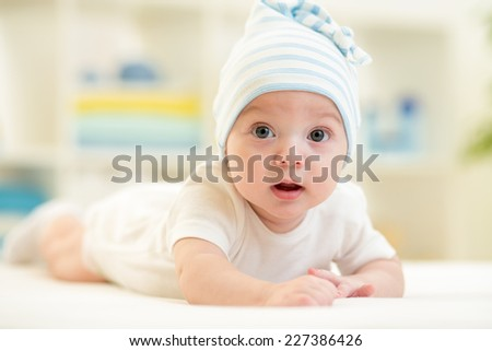 cute baby boy lying on bed in nursery - stock photo