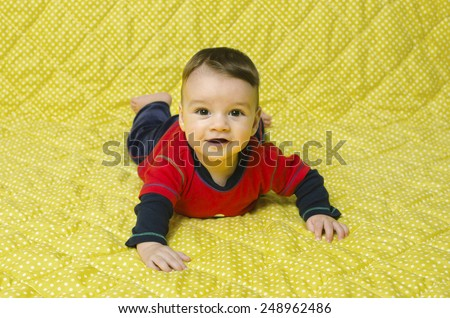 Cute baby boy lying on his belly. Happy six month baby smiling having tummy time. - stock photo