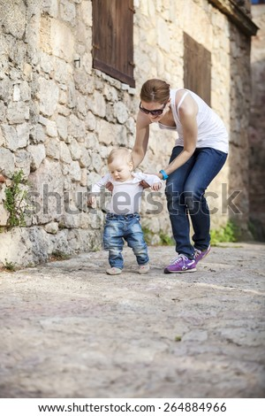 Cute baby boy makes his first steps with help of his mother - stock photo
