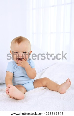 Cute baby boy on bed in room - stock photo