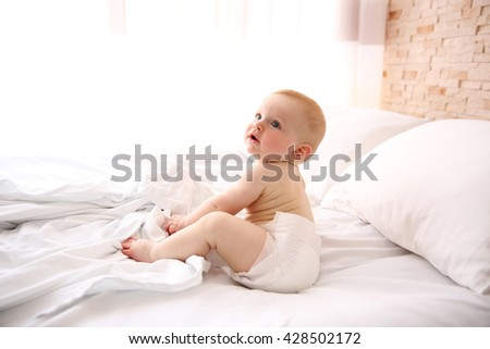 Cute baby boy on the bed - stock photo