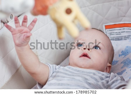 cute baby boy playing in the cradle with mobil - stock photo