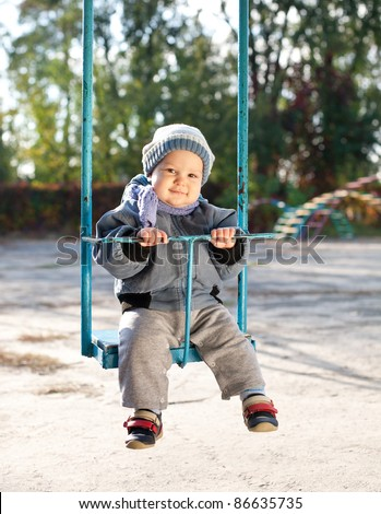 cute baby boy playing on swing in autumn park - stock photo