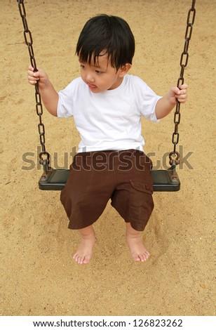 Cute baby boy playing swing - stock photo